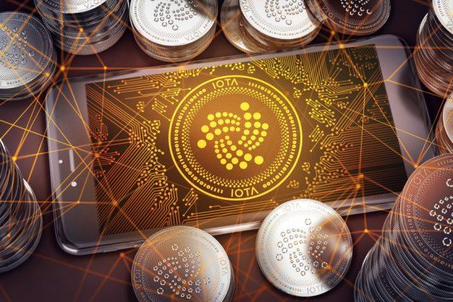 Grafik mit Smartophone, IOTA Coins und IOTA Logo