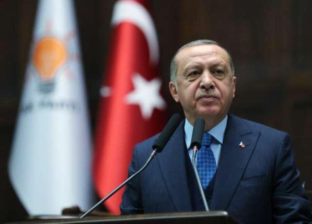 Der türkische Präsident Erdogan steht vor einem Rednerpult. Dahinter sieht man die türkische Flagge.