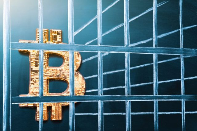 Bitcoin-Symbol hinter Gittern. Symbolbild Bitcoin-Verbot.