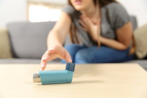 woman reaches for asthma inhaler