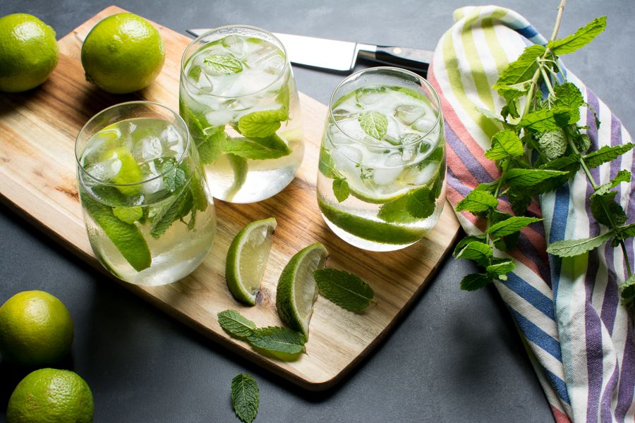 Three glasses of mojito on a cutting board with lime and fresh mint leaves
