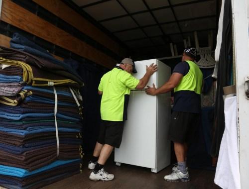 men loading a fridge to a truck