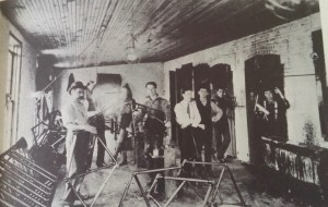Sherwood Anderson working in a Clyde bicycle factory. He is the young man in the middle with the upturned collar holding the bike frame.
