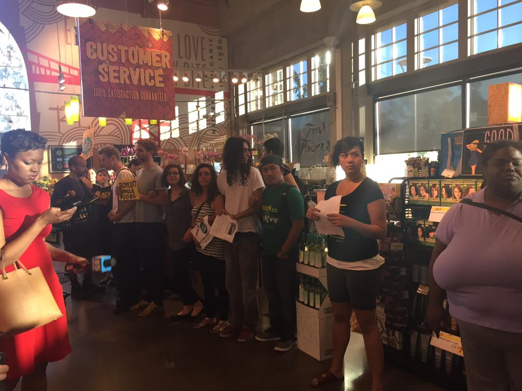 Protesters, including the author, link arms to block checkout aisles. Image by Julia Carrie Wong via Twitter