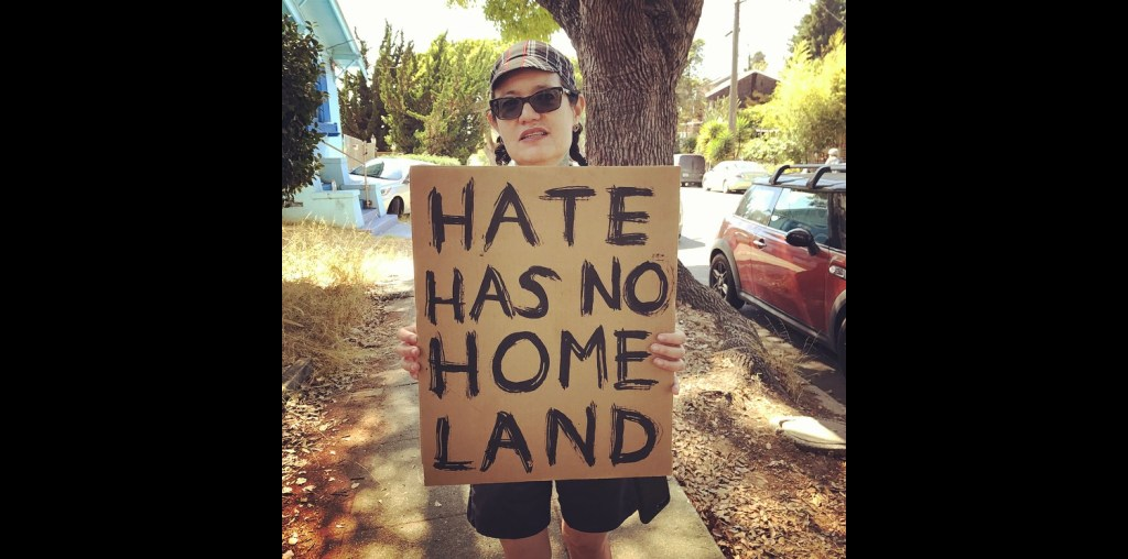 "Light-skinned poc with dark hair in twin braids, wearing sunglasses and a plaid cap, holds a hand-painted cardboard sign with big black all-caps letters: ""HATE HAS NO HOMELAND."""