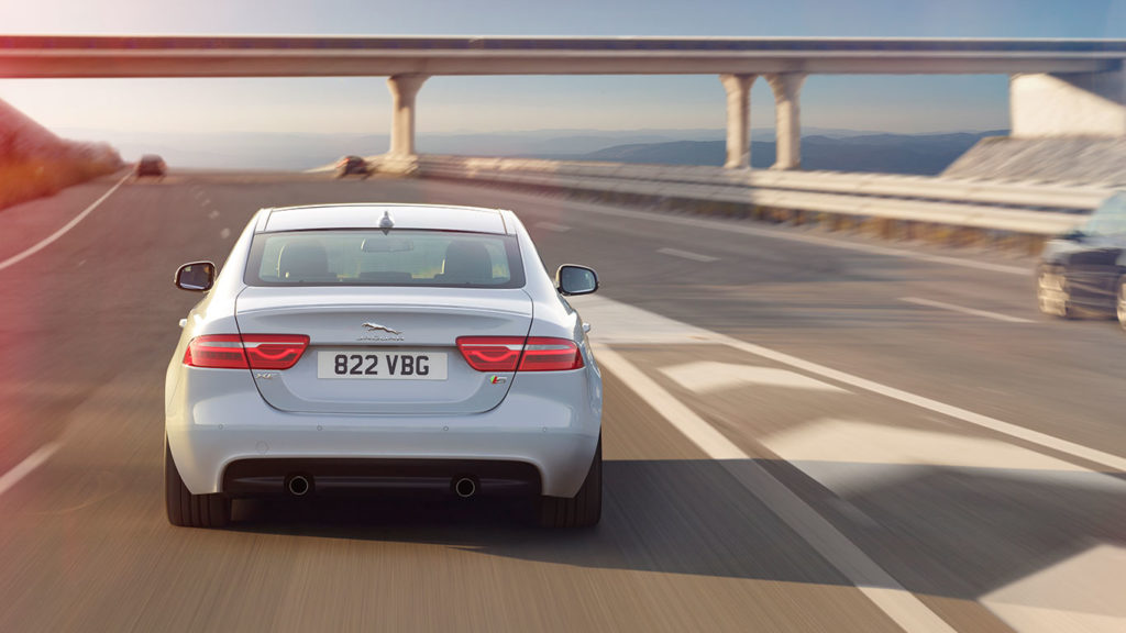 White Jaguar XE driving down sunny highway, water in distance