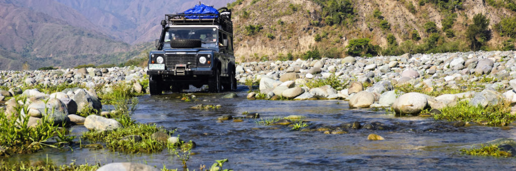 Quirino, Philippines - March 31, 2007: A Land Rover traverses the long dry river in Quirino, Philippines.