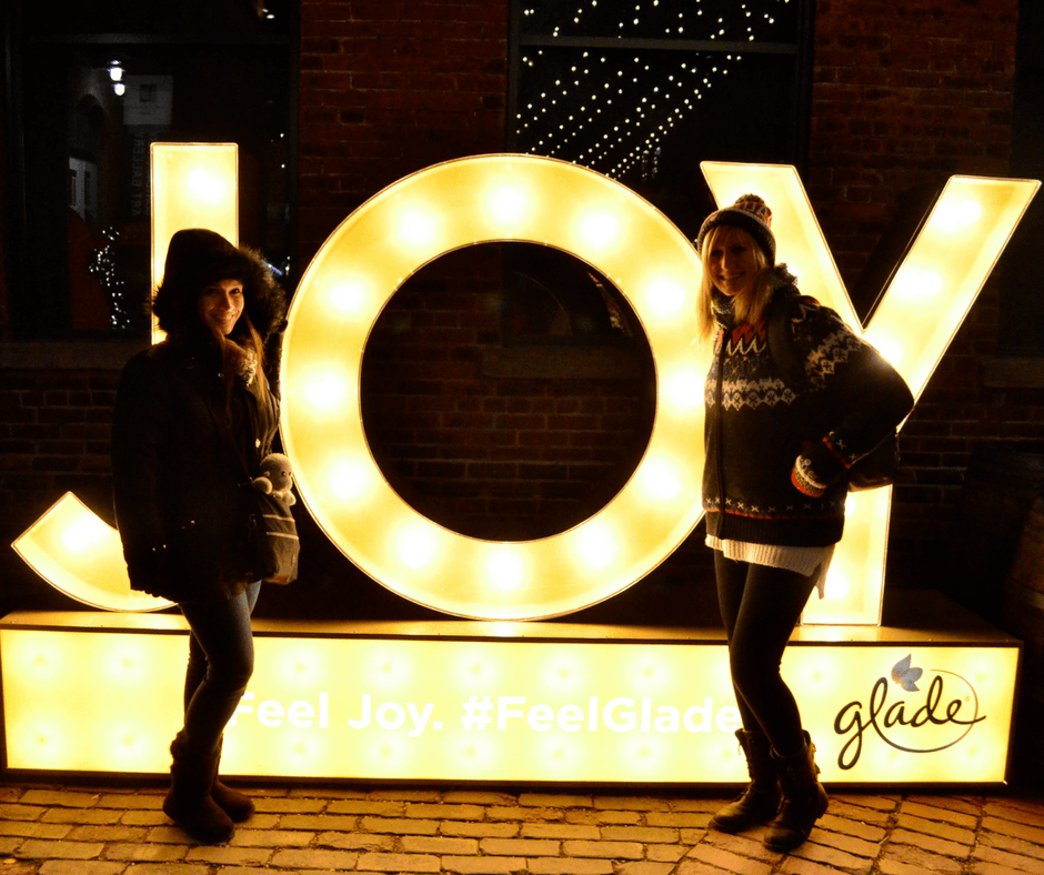 Vicky and Lindsay in front of the Joy sign at the Toronto Christmas Market