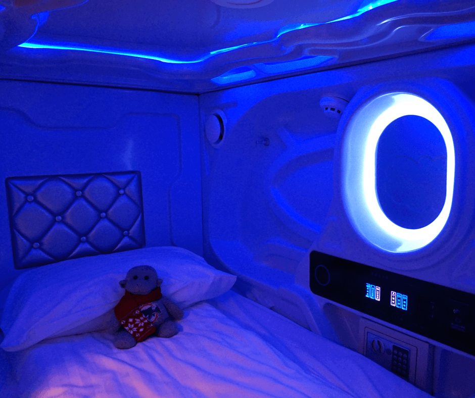 inside of a pod at the galaxy pod hostel with lights, a safe, alarm clock, shelf, and power plugs
