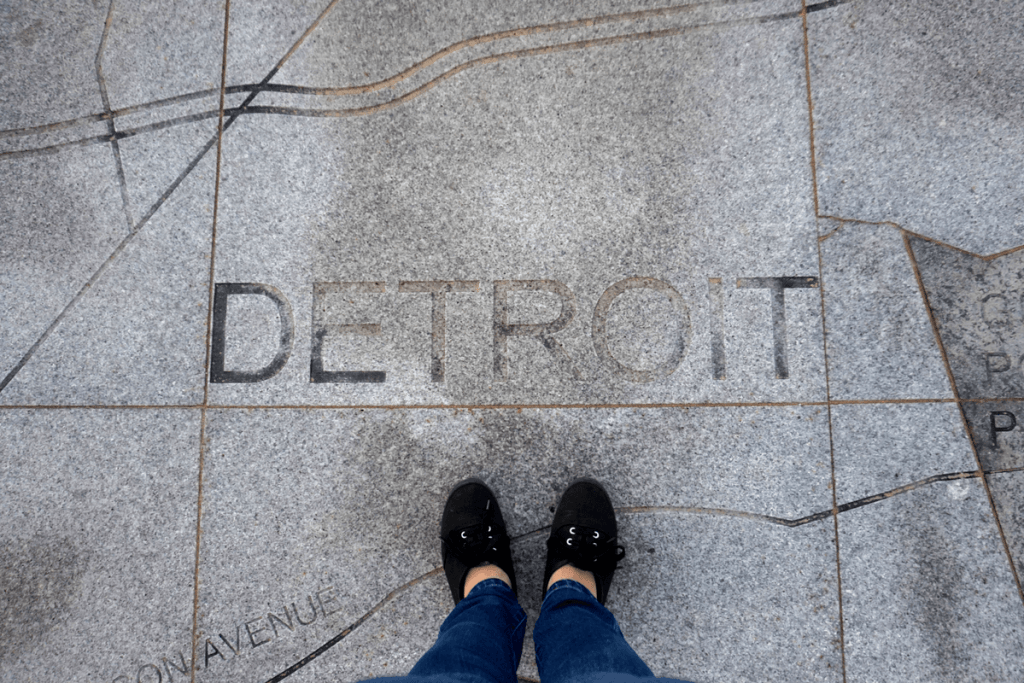 standing over Detroit on sidewalk