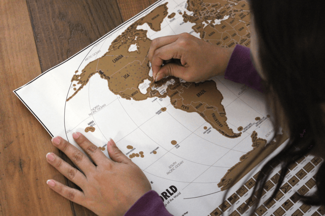scratching off countries on world travel tracker map