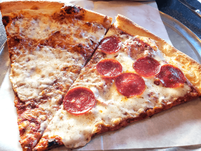 Two pizza slices at Marietta Pizza Co, one of the many Marietta Square restaurants