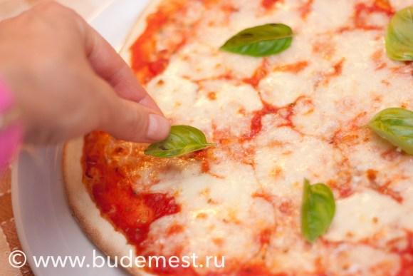 Базилик укладывается на пиццу после того, как она запеклась