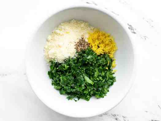Chopped parsley, lemon zest, Parmesan, and pepper in a bowl