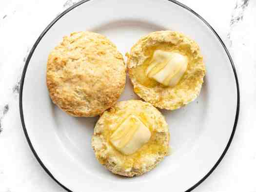 Two butter biscuits on a plate, one sliced open and topped with butter and honey