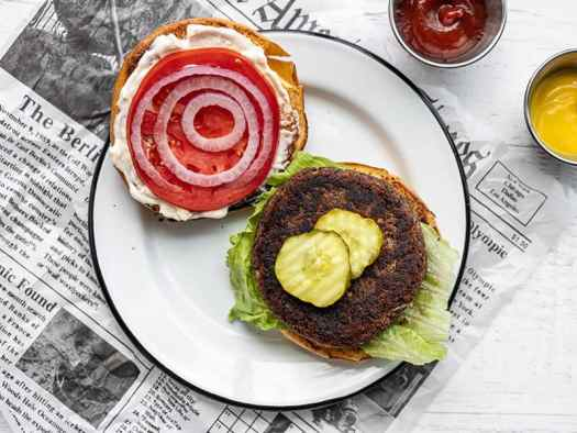 A black bean burger on a plate, dressed but open faced with ketchup and mustard on the side