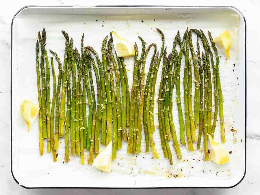 Lemon Garlic Rosted Asparagus on a sheet pan with lemon wedges
