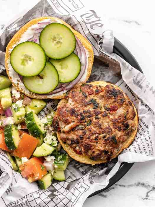 Overhead view of a mediterranean turkey burger, top bun off, on a paper lined plate next to cucumber salad