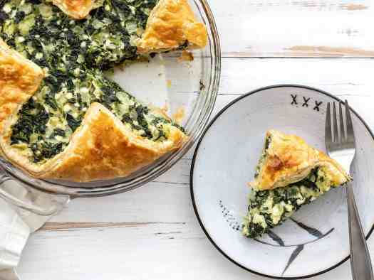 One slice of spinach pie on a plate next to the pie dish