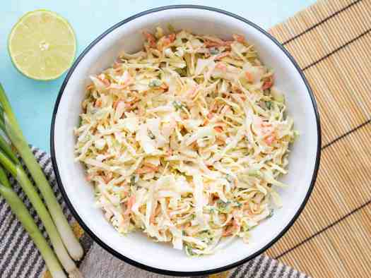 overhead view of a bowl full of cumin lime coleslaw with green onion and limes on the side