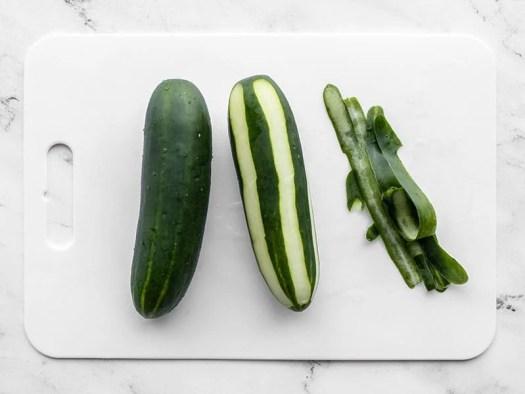Two cucumbers, one half peeled