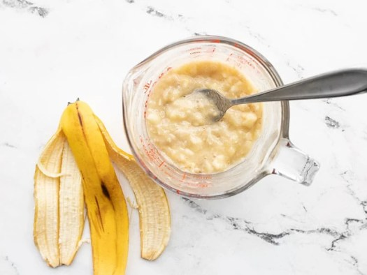 Mashed banana in a measuring cup next to a banana peel