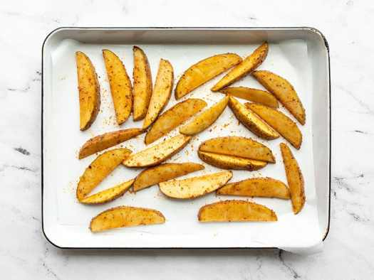 Potato wedges spread out on the parchment lined baking sheet