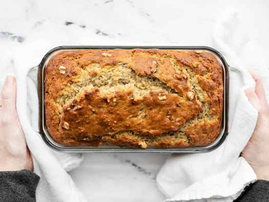 Baked yogurt banana bread being held by two hands with white towels