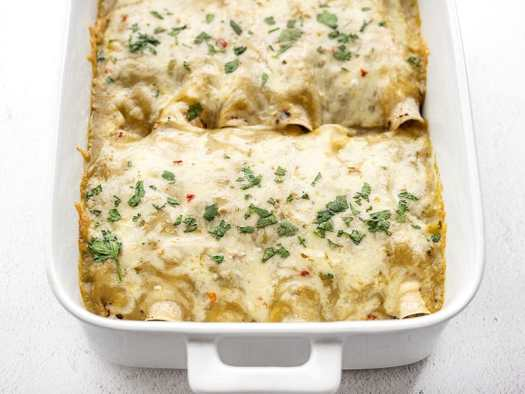 front view of green chile chicken enchiladas in the casserole dish