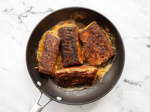 finished blackened salmon in the skillet
