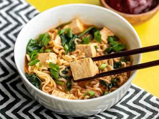 side view of a bowl of gochujang ramen with chopsticks picking up a piece of tofu