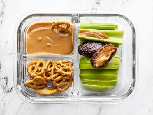 A single peanut butter lunch box with peanut butter on a Medjool date and a pretzel dipping into the peanut butter
