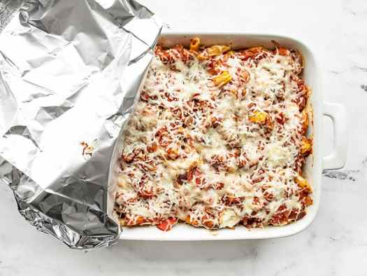 Baked Penne casserole with foil covering half the dish