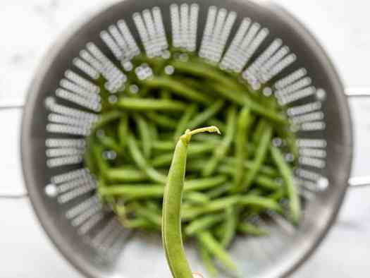Close up of a green bean with stem, more green beans in a colander in the background