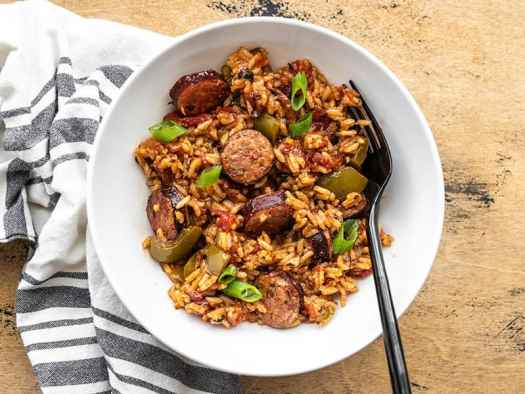 Overhead view of a bowl full of Cajun Sausage and Rice with a black fork in the side