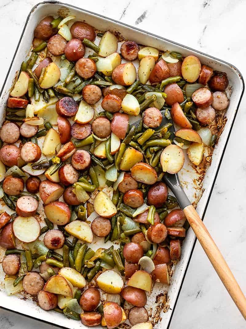 Sheet pan kielbasa, potatoes, and green beans with a spatula