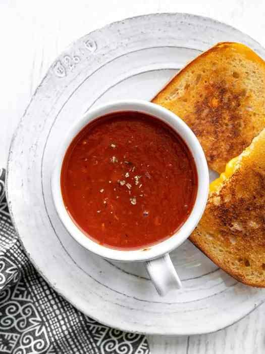 A mug of tomato herb soup on a plate with a grilled cheese