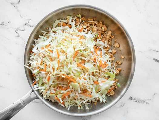 shredded cabbage and carrots added to the skillet