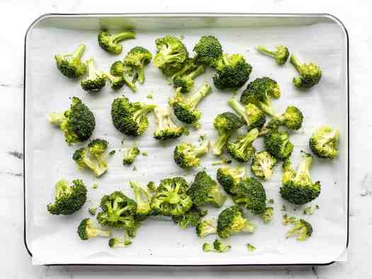 Seasoned broccoli florets on a parchment lined baking sheet