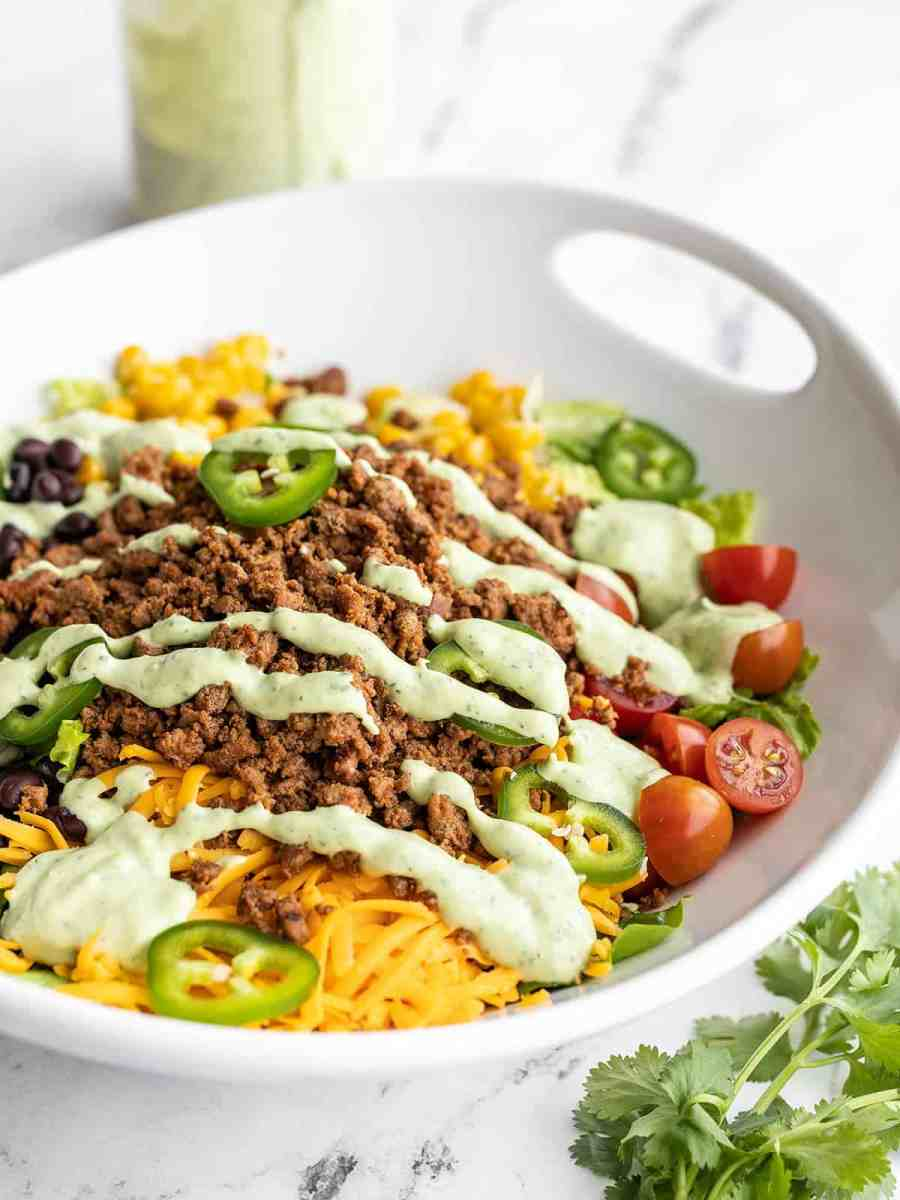 Side view of turkey taco salad in a serving bowl with the jar of dressing in the back