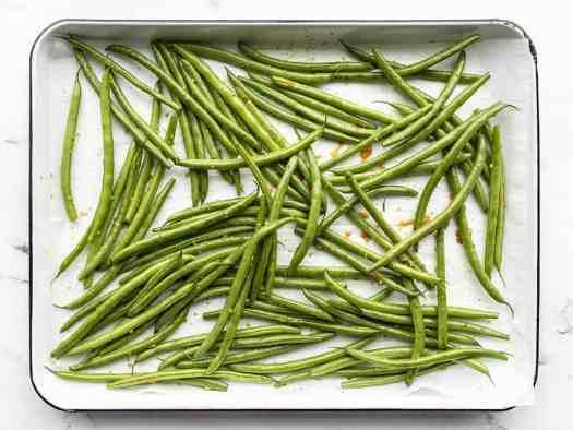Seasoned green beans on the baking sheet