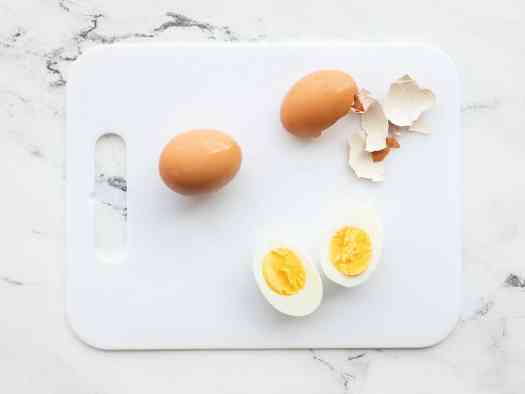 Two eggs on a cutting board, one peeled and cut in half