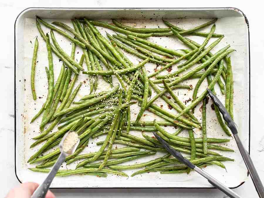 Mostly roasted green beans, sesame seeds being sprinkled on top