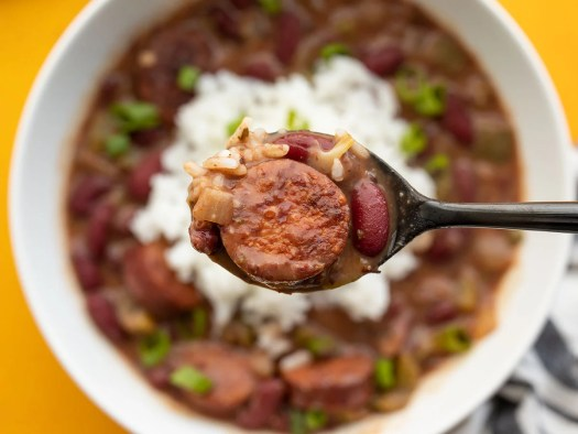 Close up of a spoonful of quickie red beans and rice with the bowl in the background