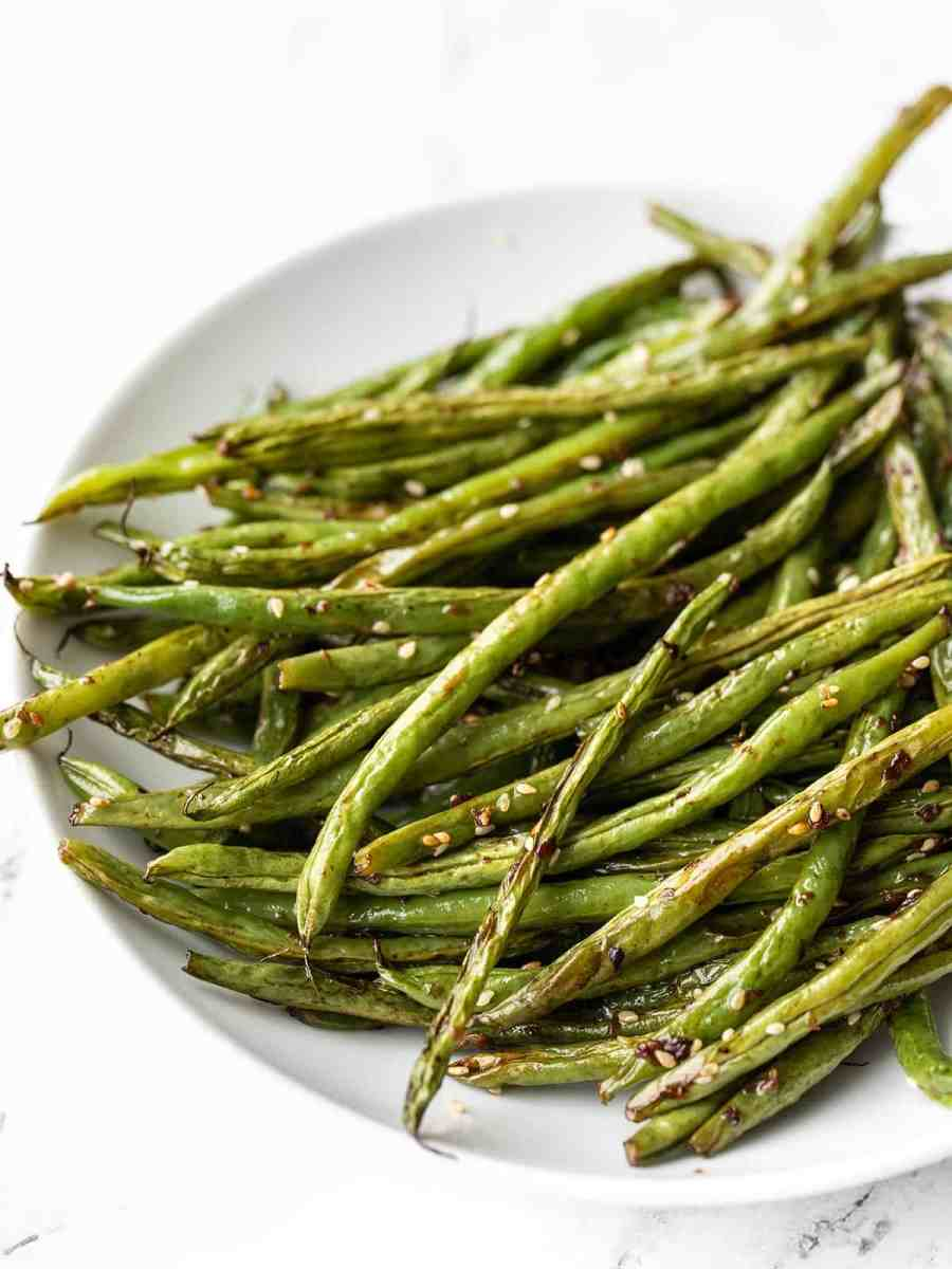 Close up side view of sesame roasted green beans in a shallow bowl