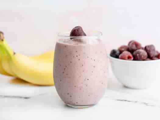 A glass filled with a cherry almond smoothie with bananas and a bowl of frozen cherries in the back