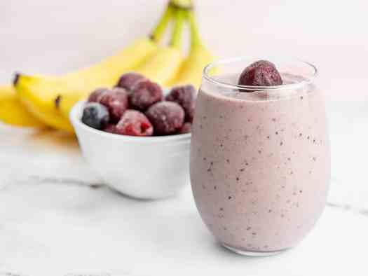 A glass filled with a cherry almond smoothie, with bananas and a bowl of frozen cherries in the back