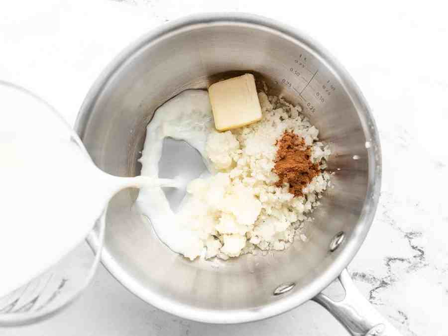 cauliflower, butter, and spices in a sauce pot, milk being poured in