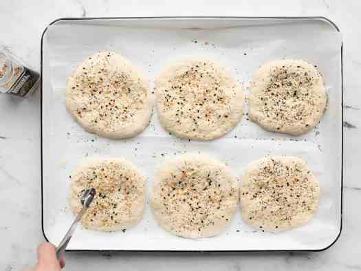 Seasoning being sprinkled on top of sandwich rounds