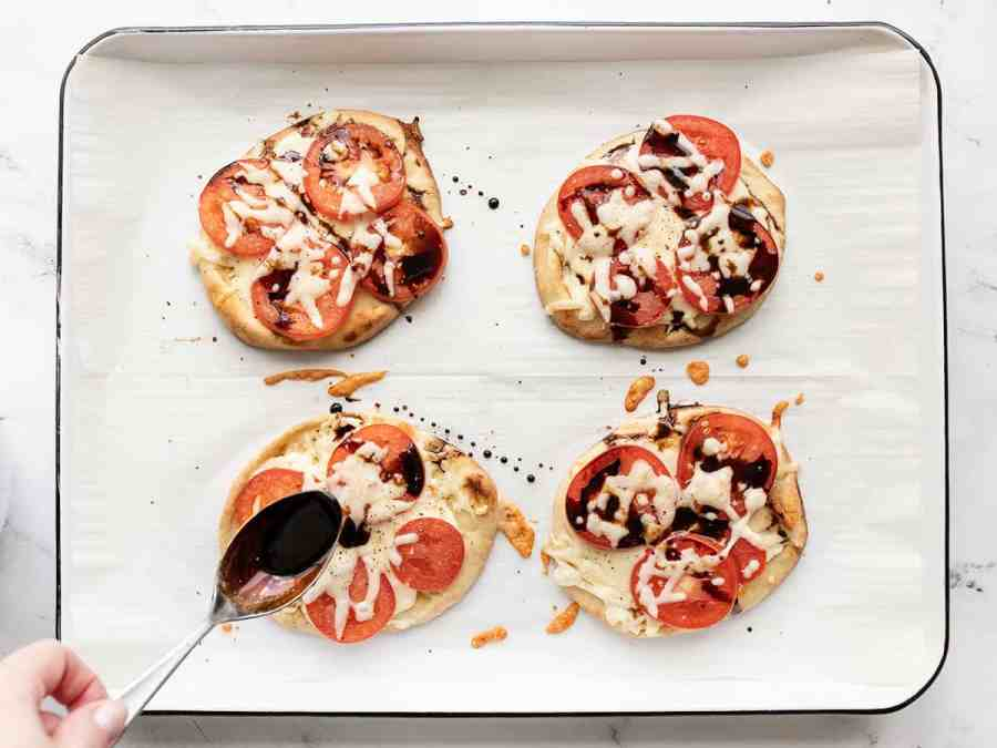 Balsamic glaze being drizzled over the pizzas